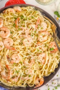 overhead of a skillet full of shrimp pasta garnished with parsley and parmesan