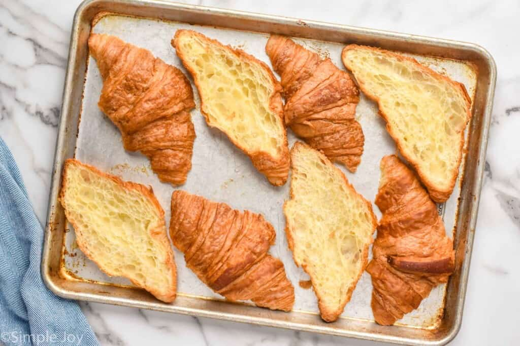 four croissants that have been cut in half and placed on a rimmed baking sheet
