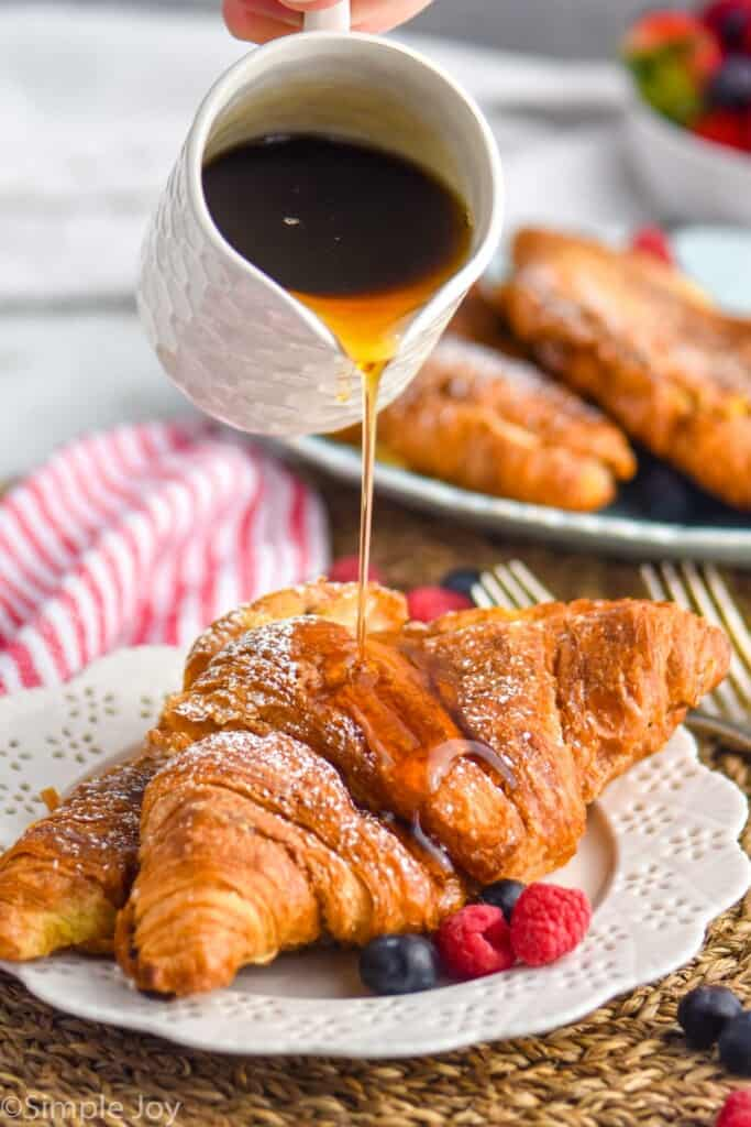 syrup being poured over croissants that have bee made into French toast