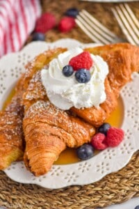 croissant French toast topped with whipped cream and berries