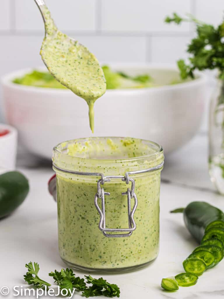 a small jar of jalapeno ranch dressing with a spoon dripping more over it