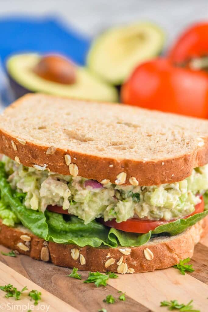 an avocado tuna salad sandwich with tomato and lettuce on a cutting board