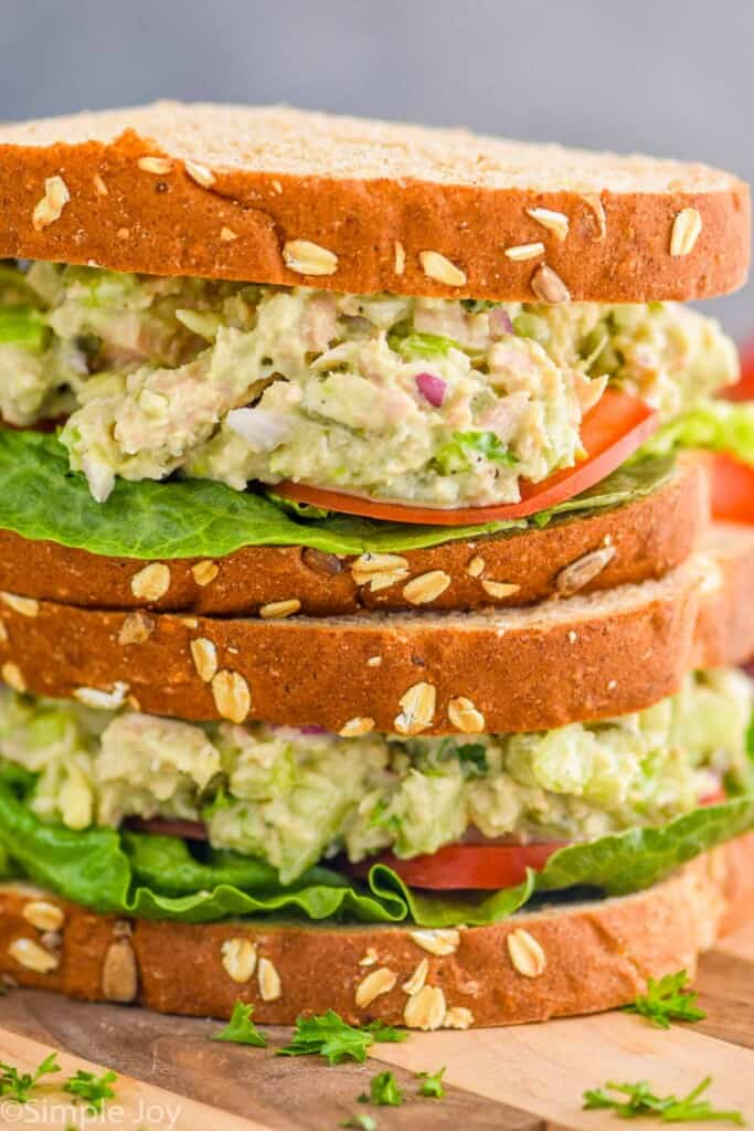 two avocado tuna salad sandwiches stacked one on top of the other