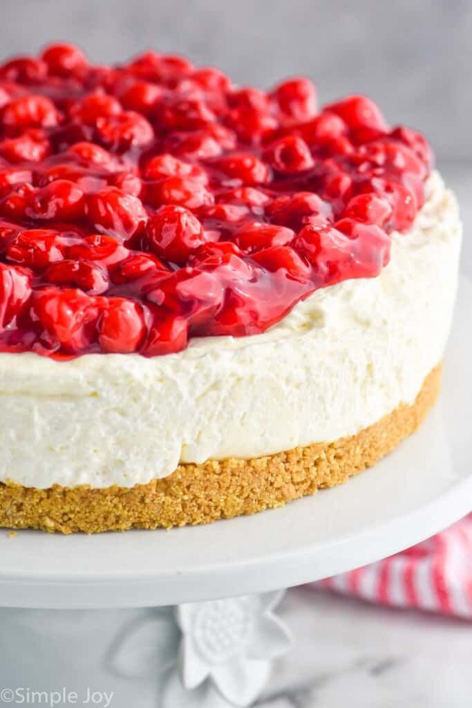 close up of a cheesecake topped with cherries on a cake stand