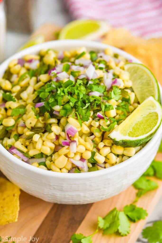 a white bowl full of chipotle corn salsa topped with extra cilantro