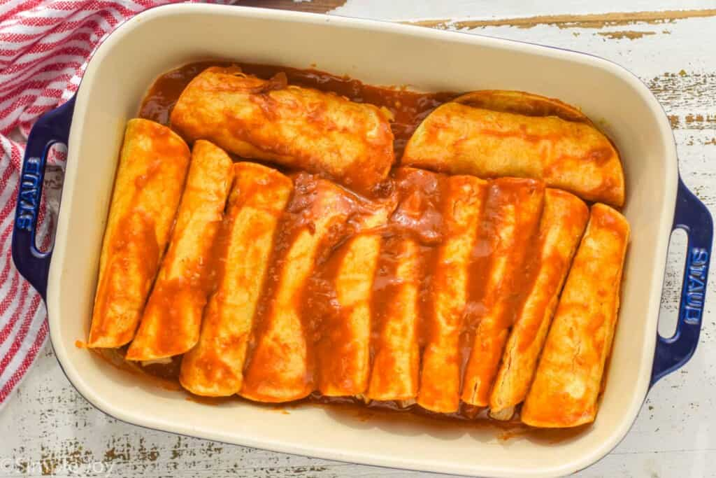 overhead of a baking dish filled with chicken enchiladas before being topped with cheese