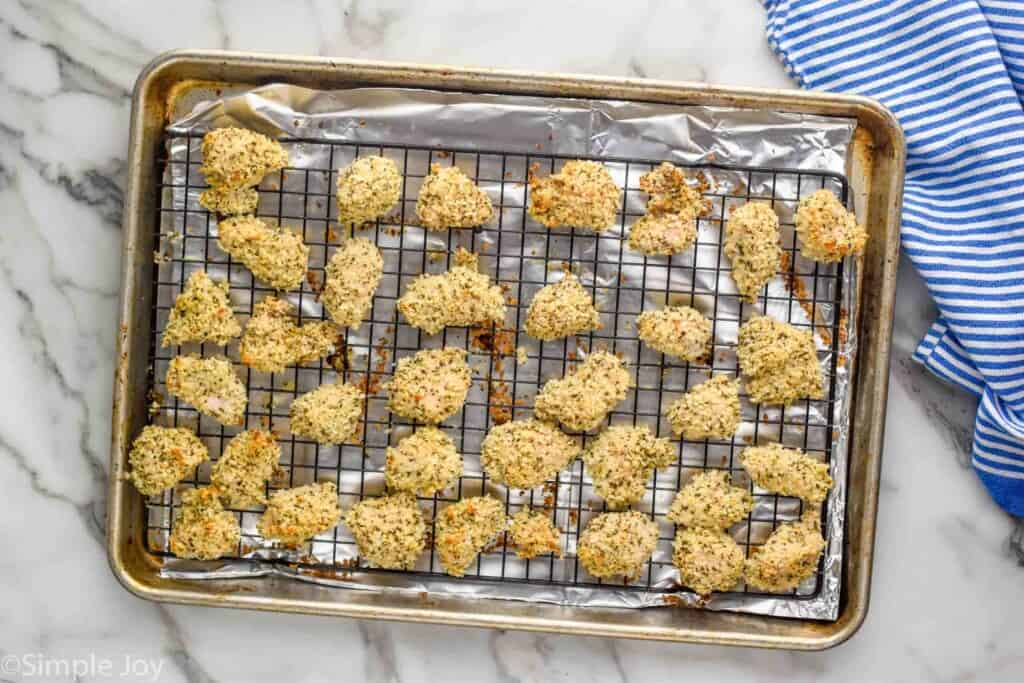 overhead of rimmed baking sheet lined with aluminum foil and cooling rack with chicken nuggets on it