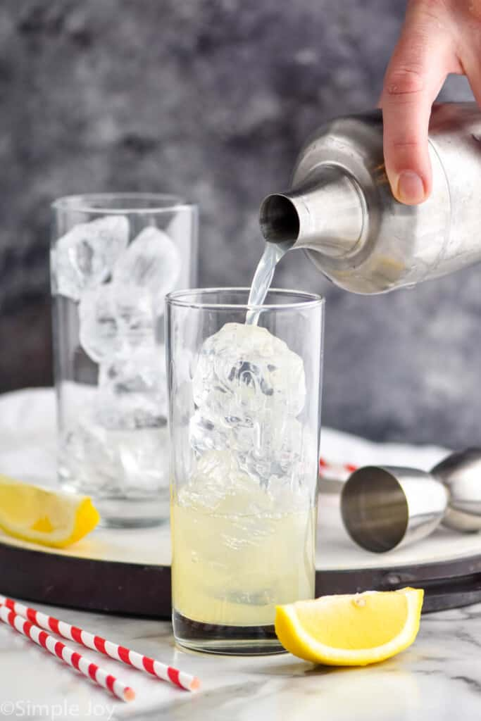 pouring mixed alcohol into a high ball glass filled with ice