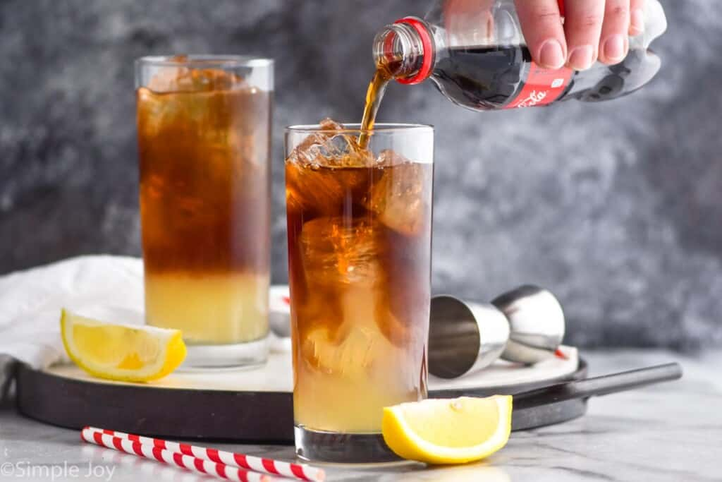 pouring coke into a high ball glass filled with ice and mixed alcohol