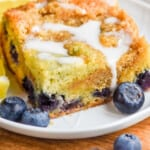 pinterest graphic of a piece of blueberry coffee cake on a plate with a drizzle of icing on top
