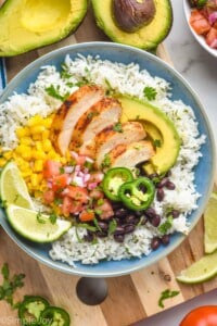 overhead of a burrito bowl with chicken, rice, avocado, beans, salsa, and corn