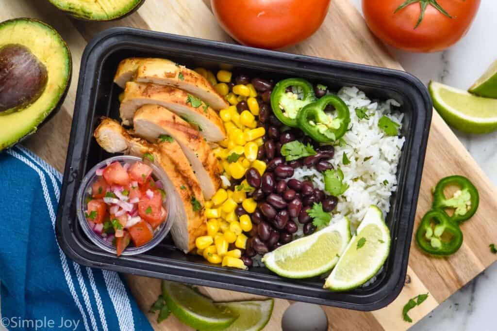 overhead of burrito bowl in a meal prep container with rice, beans, corn, chicken, and Pico de Gallo in a small cup