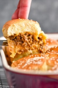 a cheeseburger slider being pulled out of a pan