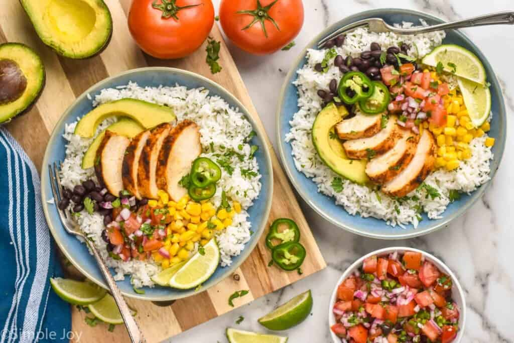 overhead of two chicken burrito bowls that have rice, corn, chicken, pico, avocado, and jalapeños