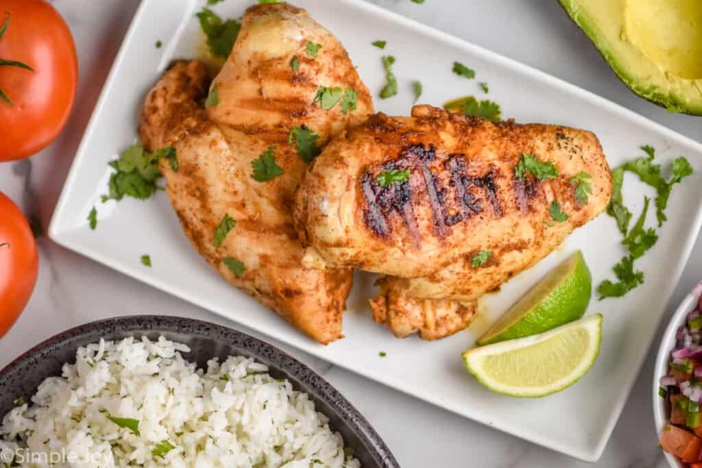 overhead of two chicken breasts on a plate that have been grilled and garnished with cilantro