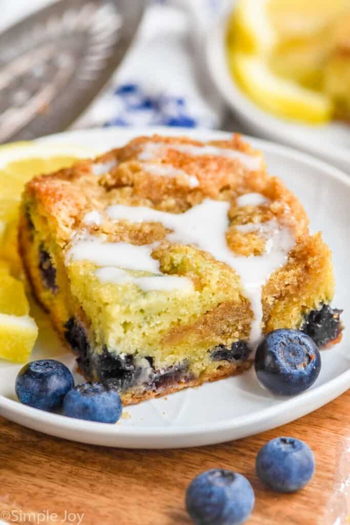 a piece of blueberry coffee cake on a plate with a drizzle of icing on top