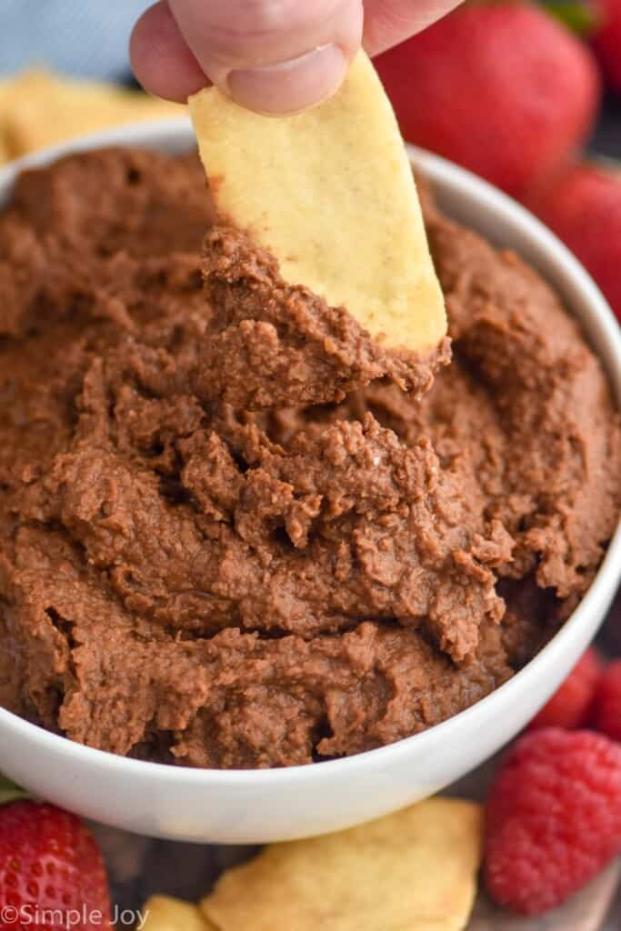close up of a pita chip dipping in dark chocolate hummus