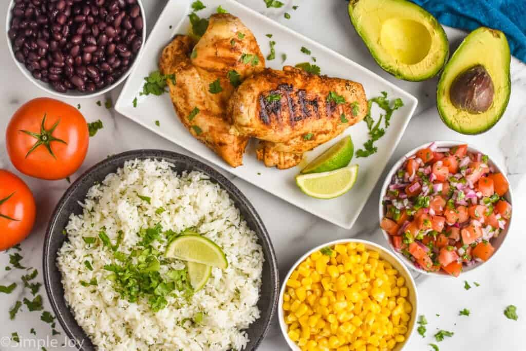 overhead of cilantro lime rice, corn, Pico de Gallo, beans, and grilled chicken in plates and bowls