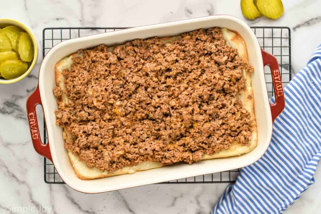 overhead of a pan of with the bottom of rolls and ground beef on top