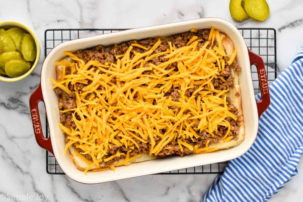overhead of a baking dish that has the bottom of rolls, ground beef, and shredded cheddar cheese