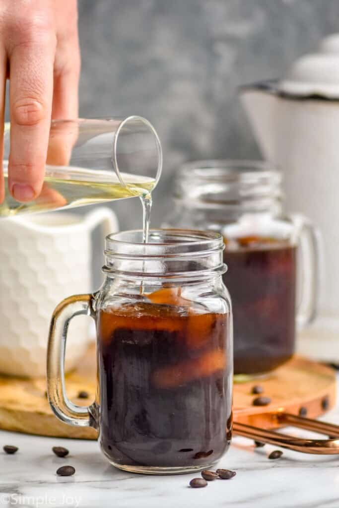 simple syrup being poured into iced coffee