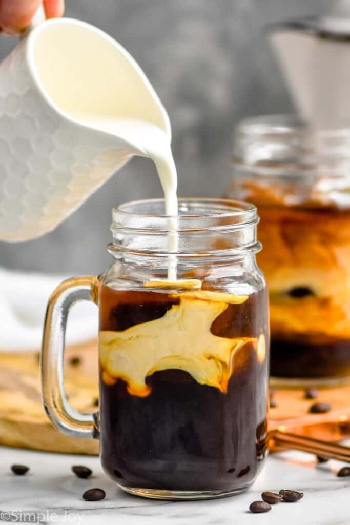 half and half being poured into an iced coffee