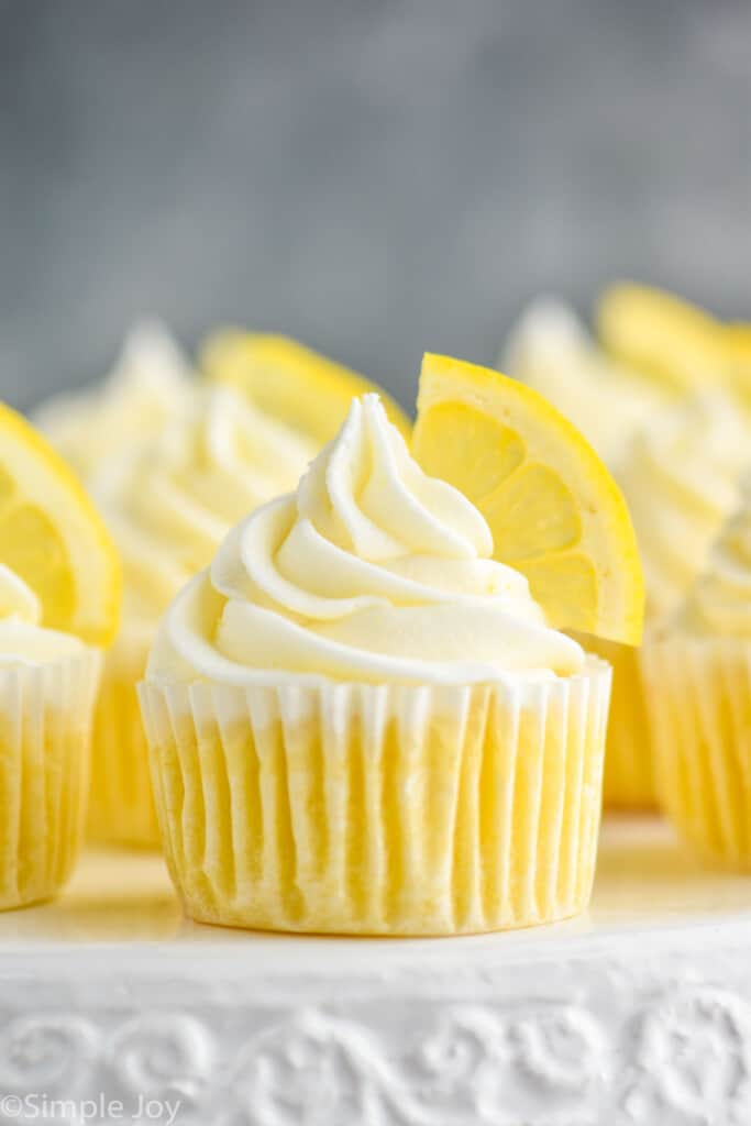 up close picture of lemon cupcakes topped with frosting swirl and a lemon wedge