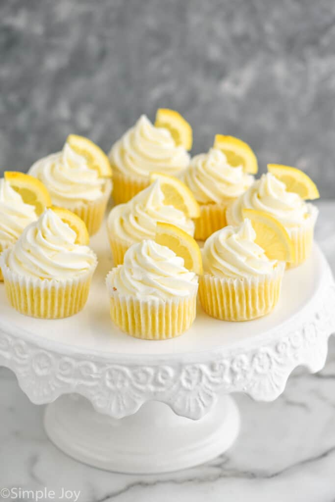 a bunch of lemon flavored cupcakes on a white cake stand