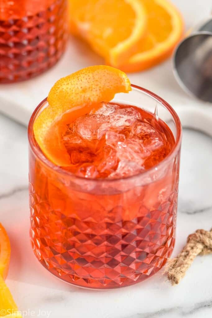 tumbler with a Negroni garnished with an orange peel