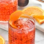 tumbler with Negroni recipe garnished with an orange peel