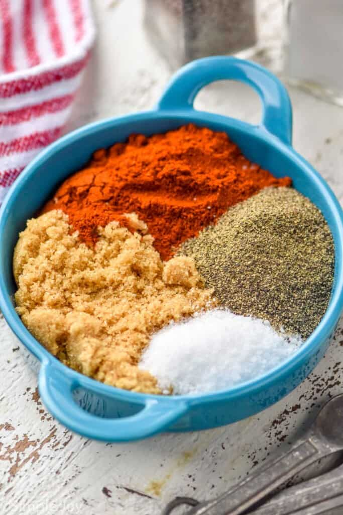 a small dish with paprika, brown sugar, salt, and pepper in it