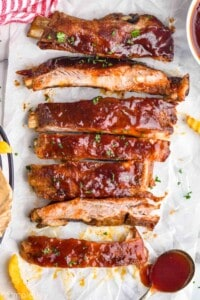 a row of slow cooker bbq ribs after being cooked, cut up on parchment paper with extra bbq sauce
