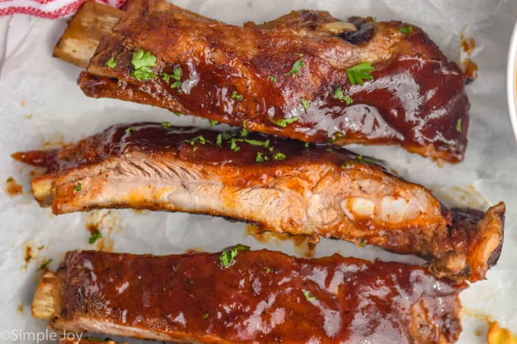 close up of slow cooker spare ribs after cooking, slathered in bbq sauce