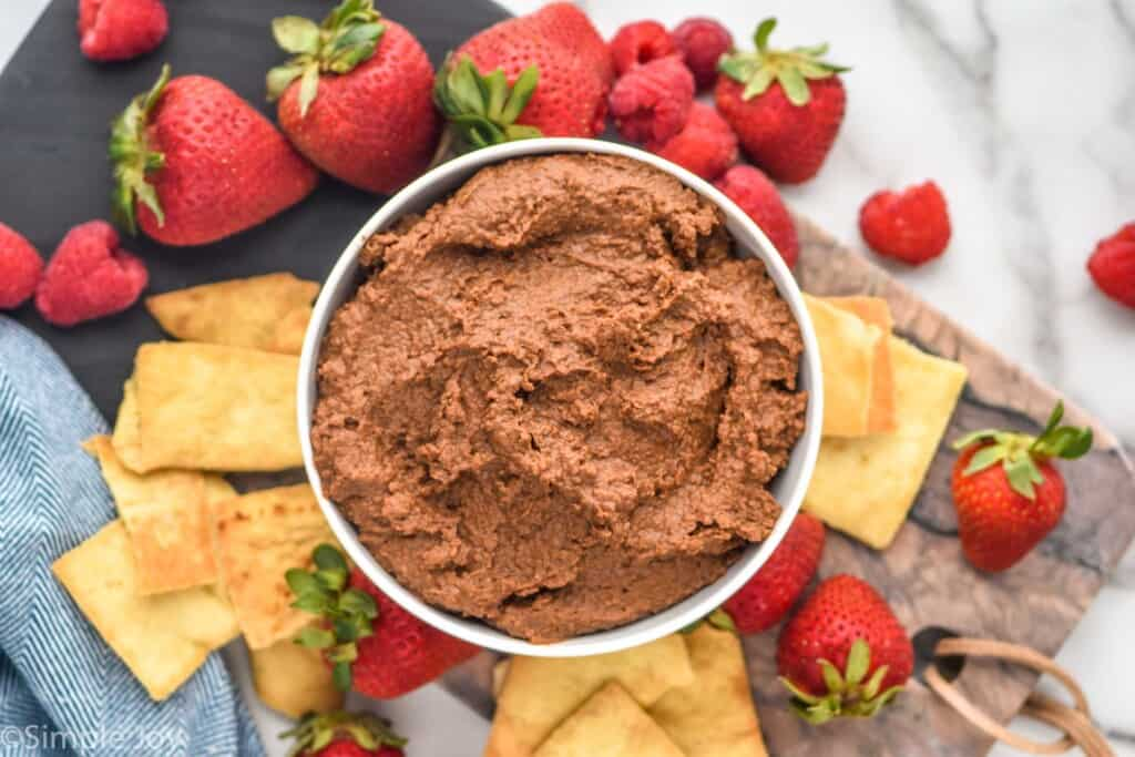 overhead of a bowl of chocolate humus on a platter with chips and berries