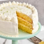 pinterest graphic of a whole key lime cake recipe on a cake stand with a piece missing