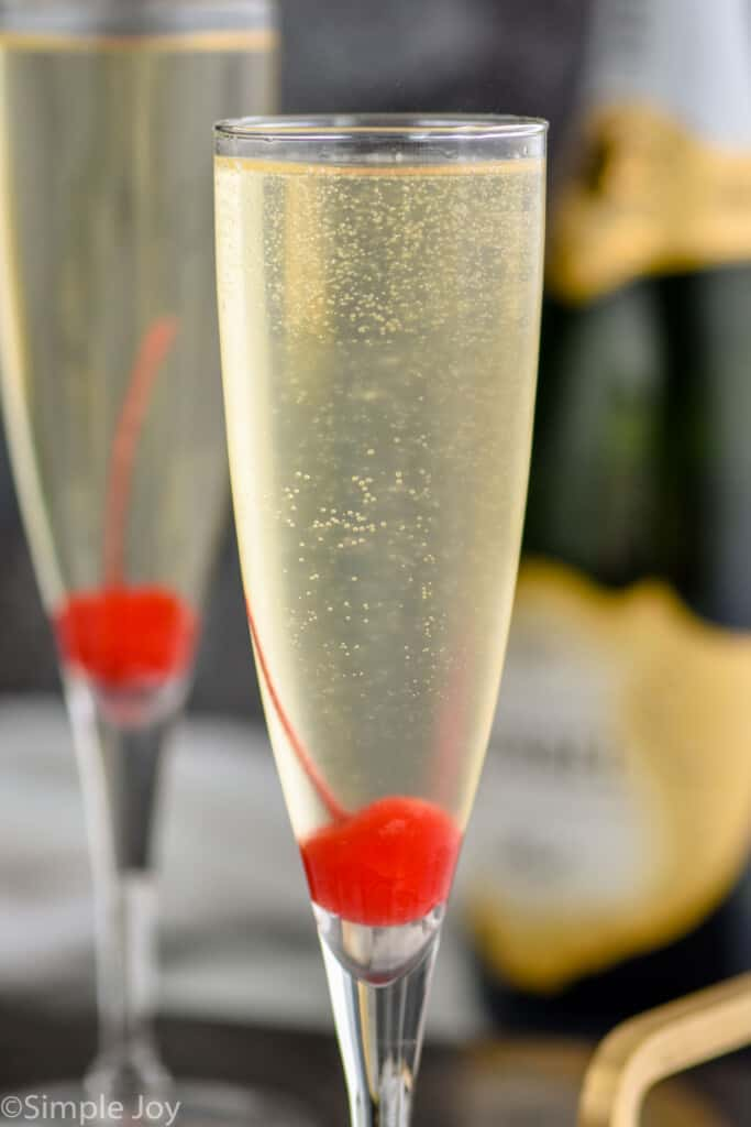close up of a champagne flute garnished with a cherry at the bottom holding a French 76 recipe