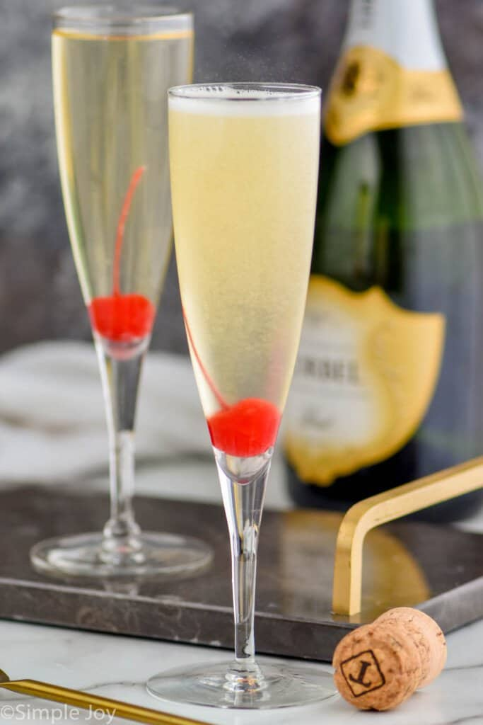 two champagne flutes with cherries at the bottom of them holding a French 76