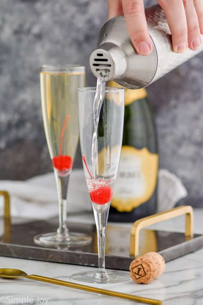 alcohol being poured into a champagne flute from a shaker