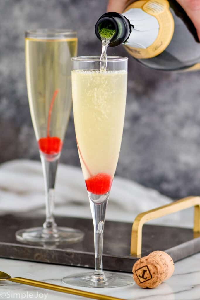 champagne being poured into a flute to top off a French 76 recipe