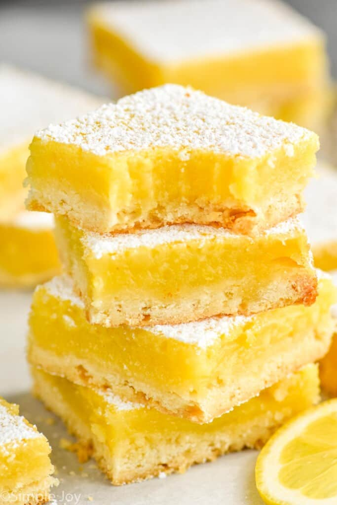 four lemon bars stacked with a bite missing out of the top one