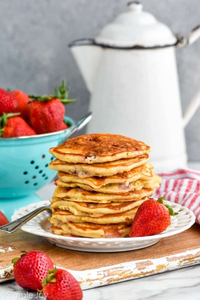 stack of strawberry pancakes on a white plate