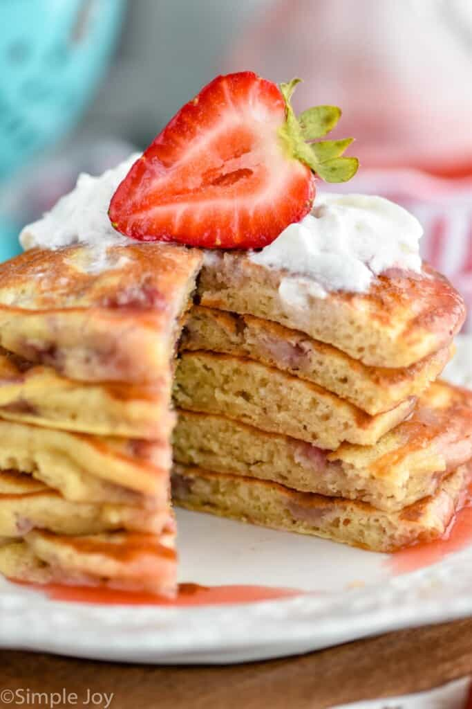 close up of strawberry pancakes with a slice missing