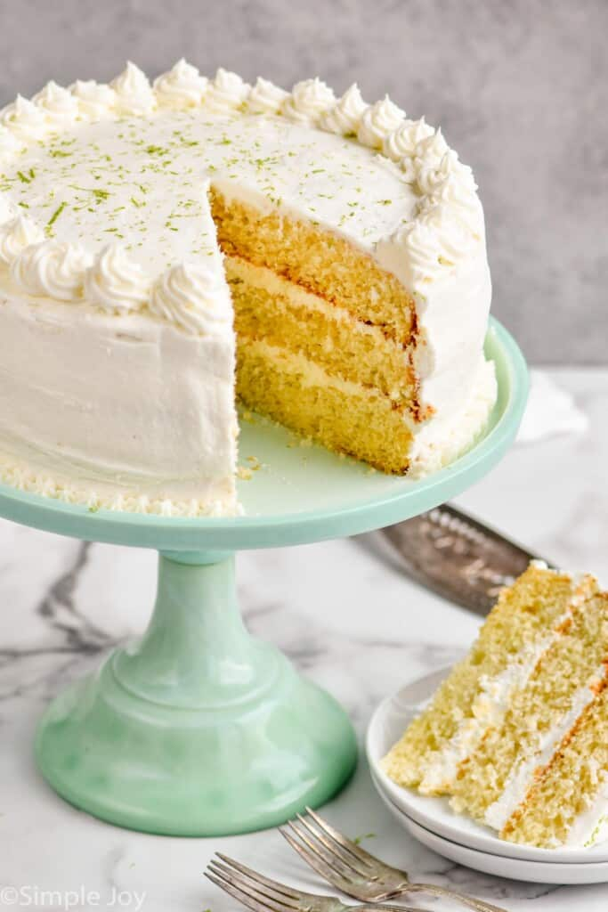 a whole key lime cake recipe on a cake stand with a piece missing