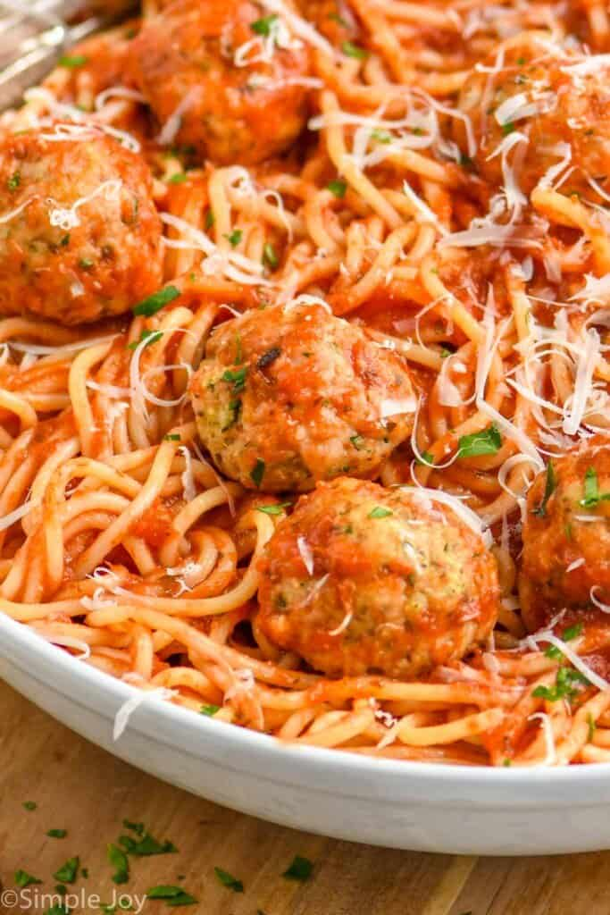close up of a chicken meatball in a bowl with spaghetti