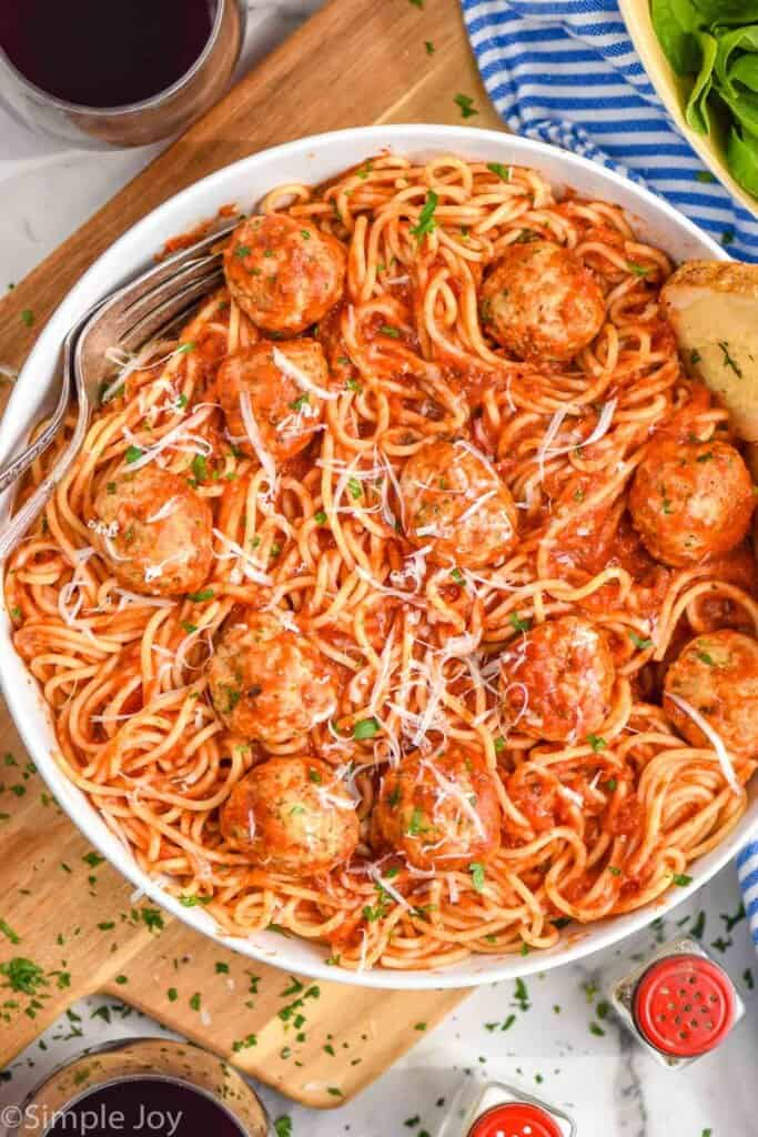 overhead of a chicken meatballs in a bowl with spaghetti, sauce covering all of it