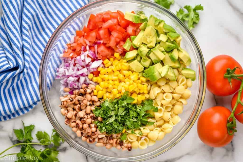 overhead of a bowl of ingredients for cowboy caviar pasta salad