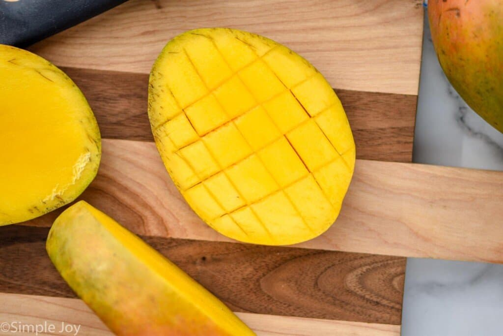 half of a mango that has been scored for easy cutting