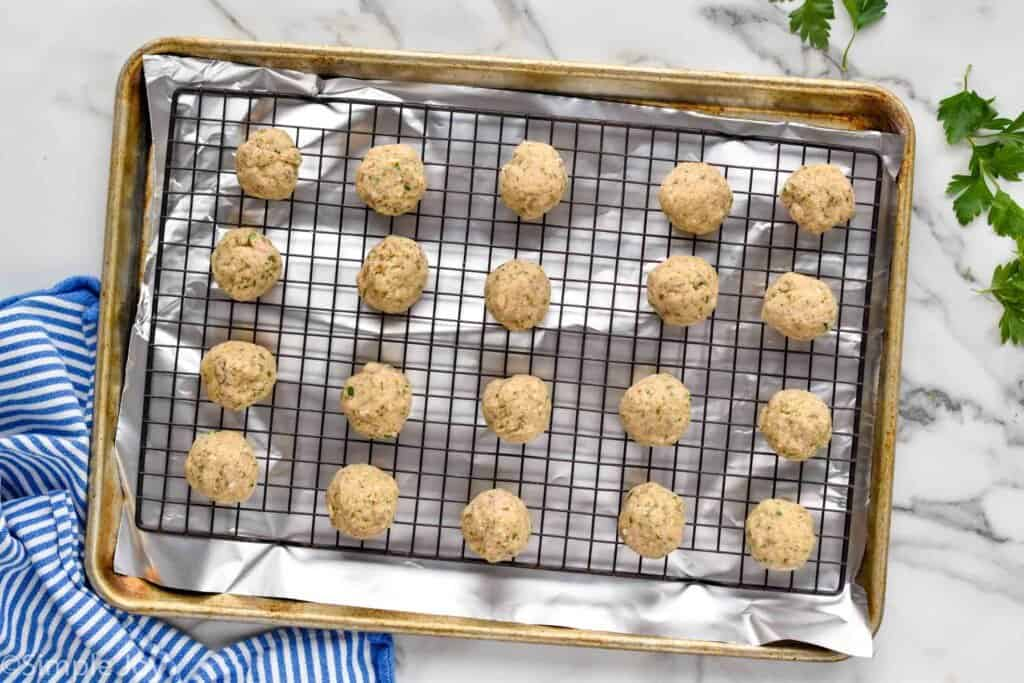 overhead of uncooked chicken parm meatballs on a cooling rack that is in a rimmed baking sheet