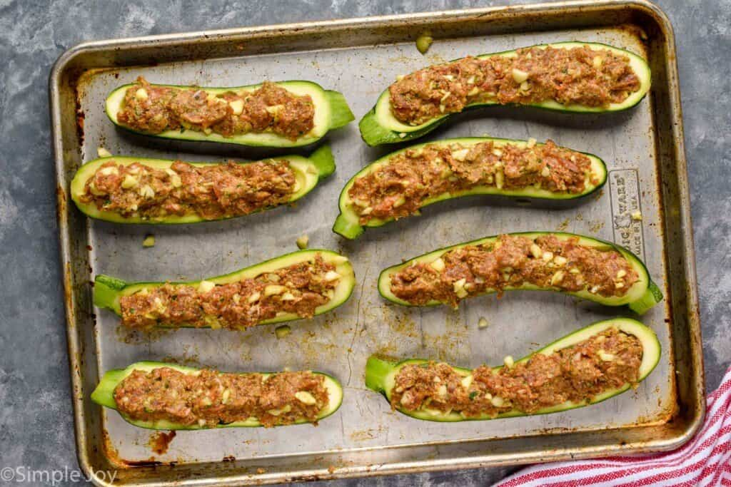 overhead of stuffed zucchini boats, uncooked on a rimmed baking sheet