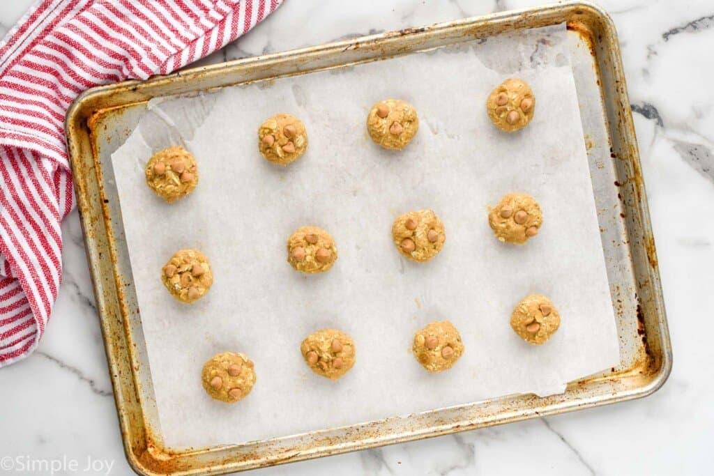 overhead of balls of oatmeal scotchies recipe dough on a baking sheet